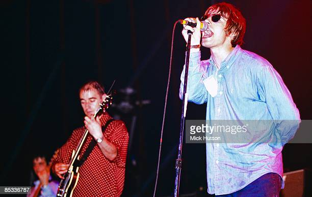 Photo of Paul Bonehead ARTHURS and Liam GALLAGHER and OASIS; Paul 'Bonehead' Arthurs and Liam Gallagher performing on stage, sunglasses