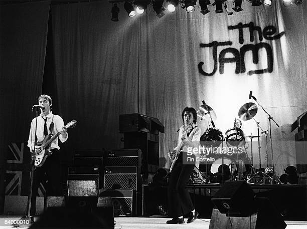 ODEON Photo of Paul WELLER and Bruce FOXTON and JAM Paul Weller Bruce Foxton Rick Buckler performing live onstage with The Jam logo on backdrop behind
