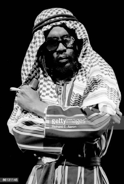 Photo of Peter TOSH Peter Tosh performing on stage dressed as arab