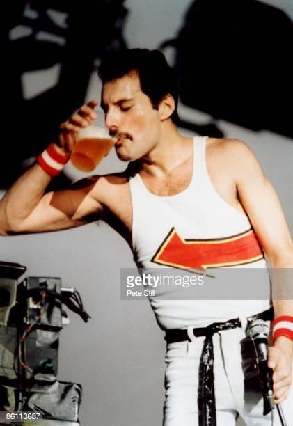 Photo of QUEEN and Freddie MERCURY, Freddie Mercury performing on stage, drink, beer