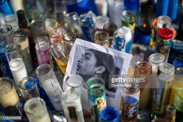 A photo of rapper Nipsey Hussle is seen among candles as people gather to mourn him on April 1 2019 in Los Angeles California The Grammynominated...