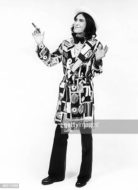 Photo of Ray DAVIES and KINKS Ray Davies posed studio wearing smoking jacket and bow tie holding cigar