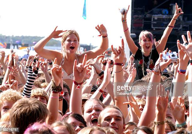 Photo of READING FESTIVAL, Two young women sitting on shoulders in audience at Reading Festival, waving, shouting, cheering, with arms in air, fans,...