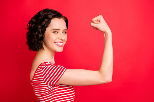 Photo of rejoicing wavy curly woman after having done two pushups while isolated with red background 1165694606