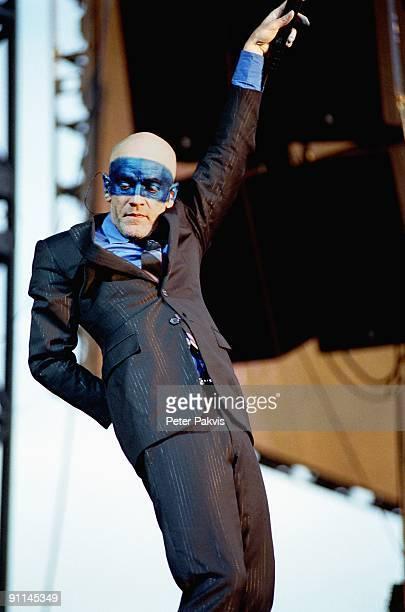 Photo of REM, REM, Nederland, Rockin' Park, Nijmegen, 26 juni 2005, Pop, wave, Micheal Stipe, wiens gelaat gedeeltelijk is be-, schilderd met blauwe...