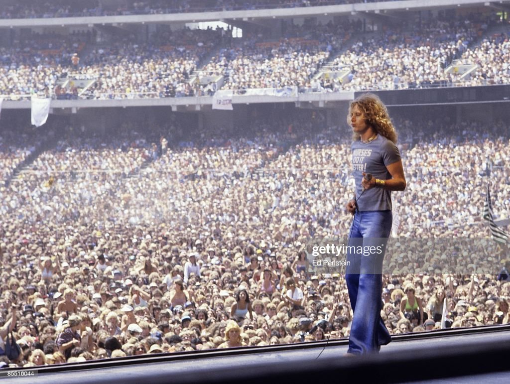 COLISEUM Photo of Robert PLANT and LED ZEPPELIN, Robert Plant performing on stage, wearing 'Nurses do it Better' t shirt, audience in photo