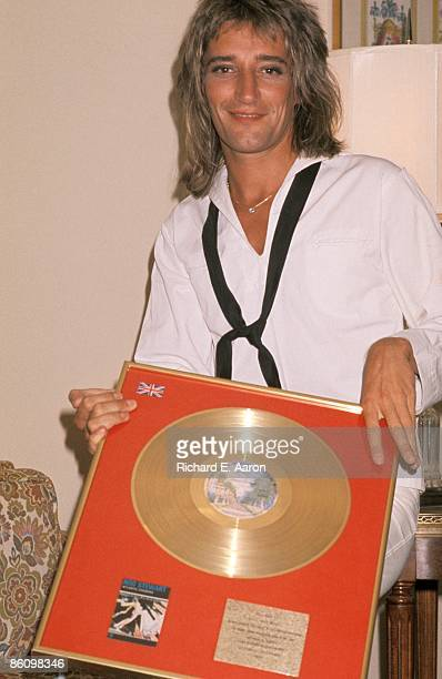 Photo of Rod STEWART; posed, in sailor costume, with Gold Disc for Atlantic Crossing album
