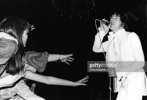 Photo of Roger DALTREY and The Who Roger Daltrey performing live onstage female fans reaching up hands from audience