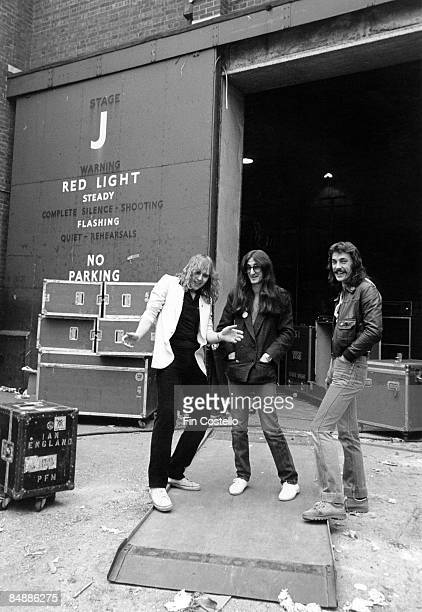 Photo of RUSH Alex Lifeson Geddy Lee Neil Peart posed group shot outside studios rehearsals on Hemispheres tour