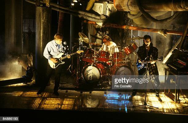 Photo of RUSH LR Alex Lifeson Neil Peart Geddy Lee performing on set of video for 'The Body Electric'