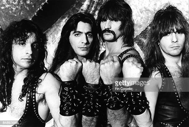 Photo of Scott COLUMBUS and Eric ADAMS and MANOWAR and Ross FRIEDMAN and Joey DeMAIO Posed studio group portrait fists up LR Eric Adams Joey DeMaio...