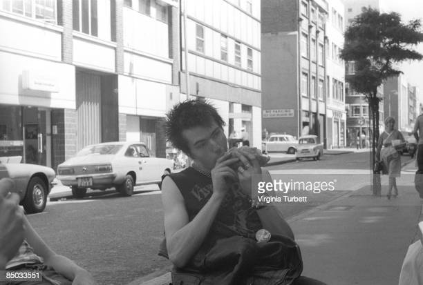 Photo of Sid VICIOUS and SEX PISTOLS Sid Vicious posed eating sandwich