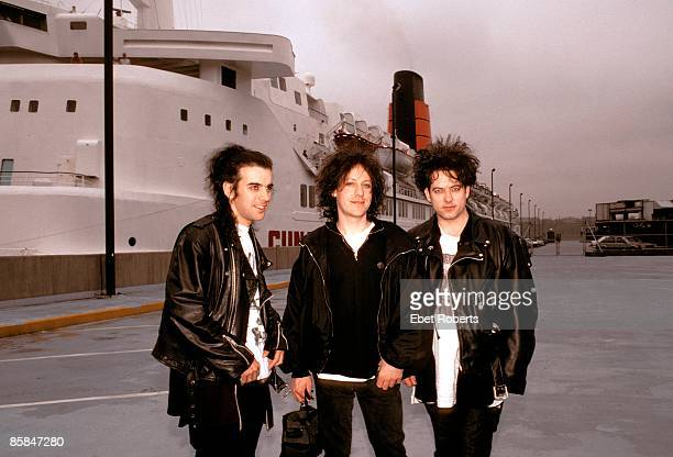 UNITED STATES MAY 01 Photo of Simon GALLUP and Robert SMITH and Perry BAMONTE and The CURE Simon Gallup Perry Bamonte and Robert Smith posed next to...