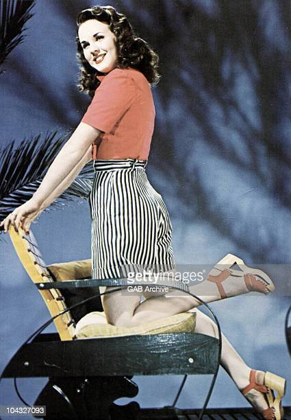 Photo of singer and actress Deanna Durbin posed on a chair