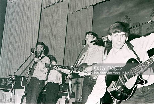 Photo of singerguitarist John Lennon singerbassist Paul McCartney and guitarist George Harrison of The Beatles live onstage circa May 1962 at the...
