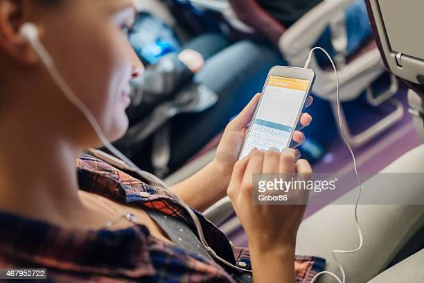 Photo of smiling young woman using smartphone on airplane
