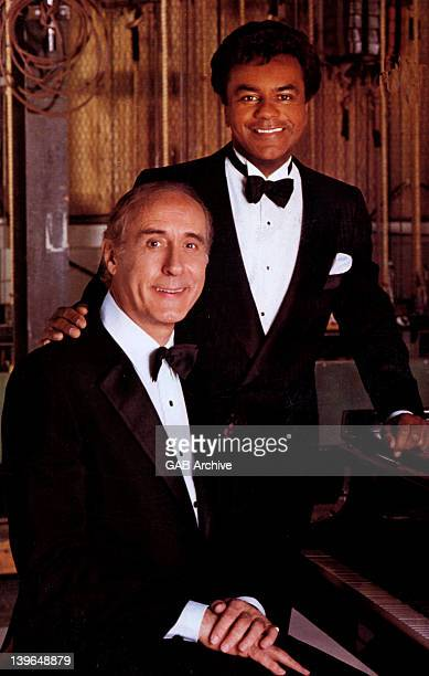 Photo of songwriter and singer Johnny Mercer posed with singer Johnny Mathis circa 1975