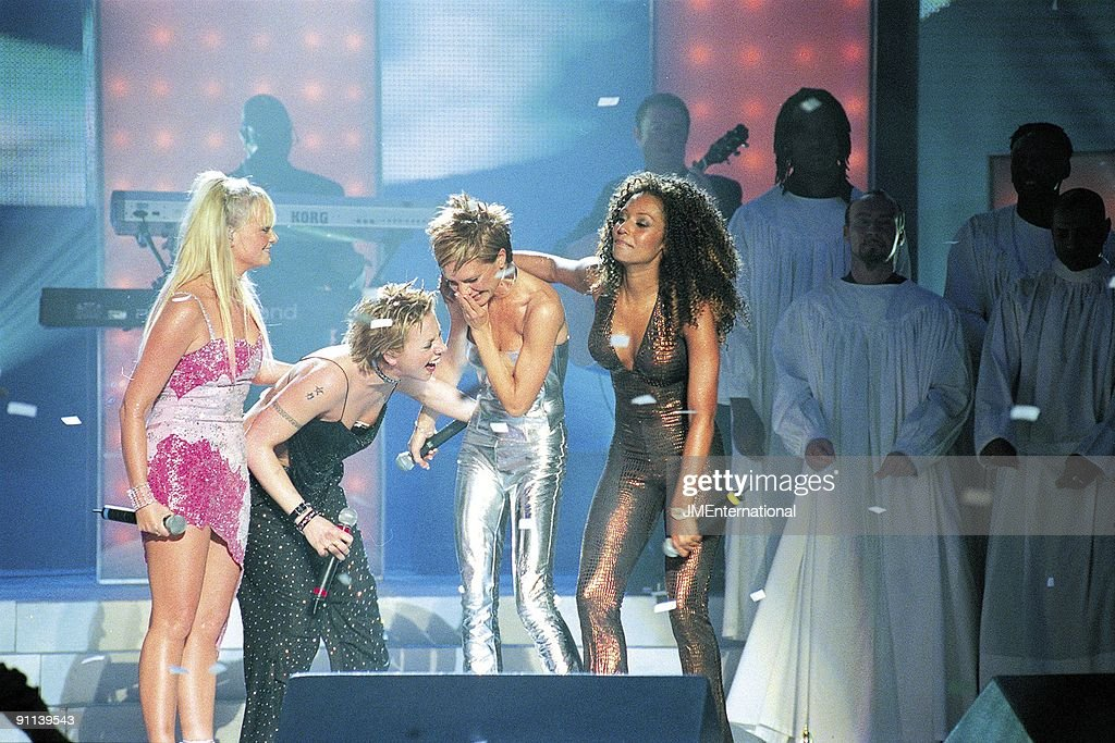 Emma Bunton, Melanie Chisholm (Mel C), Victoria Beckham and Melanie Brown (Mel B) performing live on stage, laughing