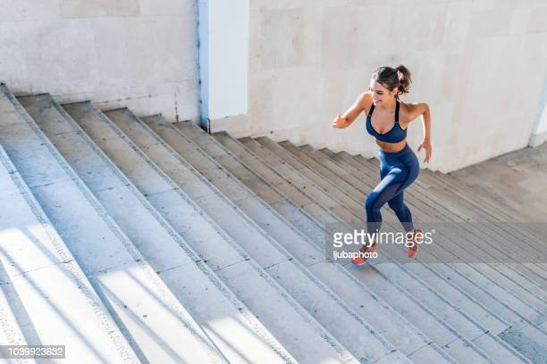 photo of sports woman running up outdoor stairway - forward athlete stock pictures, royalty-free photos & images
