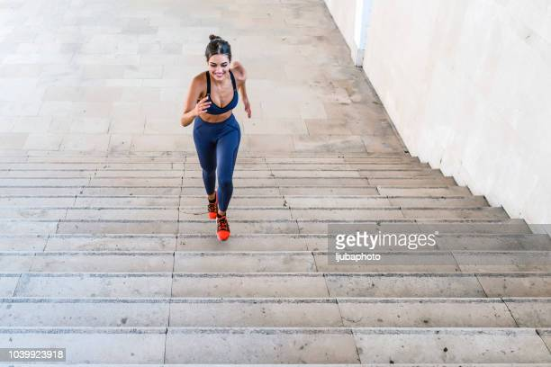 photo of sporty woman running up steps in urban setting - forward athlete stock pictures, royalty-free photos & images