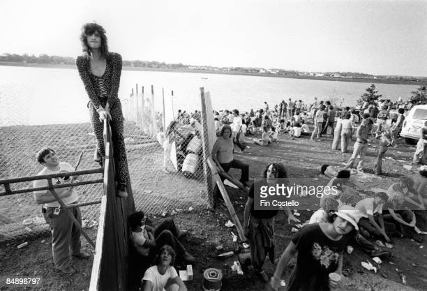 Photo of Steven TYLER and AEROSMITH Steven Tyler sitting on a fence as fans look on
