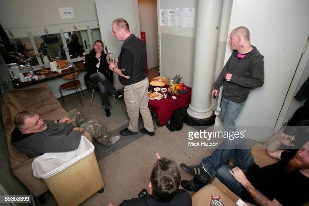 Photo of STONE SOUR and Corey TAYLOR and Shawn ECONOMAKI posed backstage in dressing room Corey Taylor top right at door Shawn Economaki bottom right