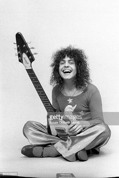 Photo of T REX and Marc BOLAN; Studio, posed, with Gibson Flying V guitar. Sitting cross legged, laughing