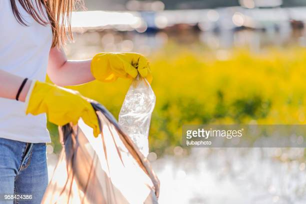 Photo of Teenager picking up garbage from river bank