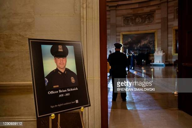 Photo of the fallen Capitol Police officer Brian Sicknick is seen as people wait for his remainsto arrive to lay in honor in the Rotunda of the US...