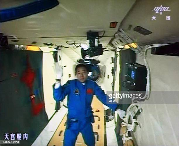A photo of the giant screen at the Jiuquan space center shows mission commander Jing Haipeng in the Tiangong1 module on June 18 2012 Three Chinese...