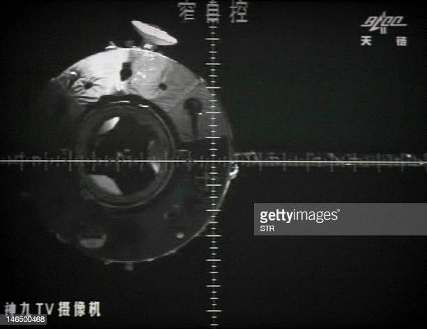 A photo of the giant screen at the Jiuquan space center shows the Tiangong1 module is seen via a camera in the Shenzhou9 spacecraft before the...