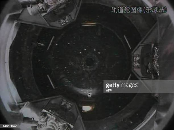 A photo of the giant screen at the Jiuquan space center shows the Tiangong1 module being filmed from the Shenzhou9 spacecraft before the automatic...