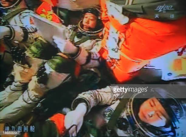 A photo of the giant screen at the Jiuquan space center shows three Chinese astronauts Liu Wang Jing Haipeng and Liu Yang in the Shenzhou9 spacecraft...