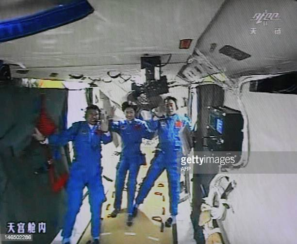 A photo of the giant screen at the Jiuquan space center shows three Chinese astronauts Liu Wang Jing Haipeng and Liu Yang in the Tiangong1 module on...