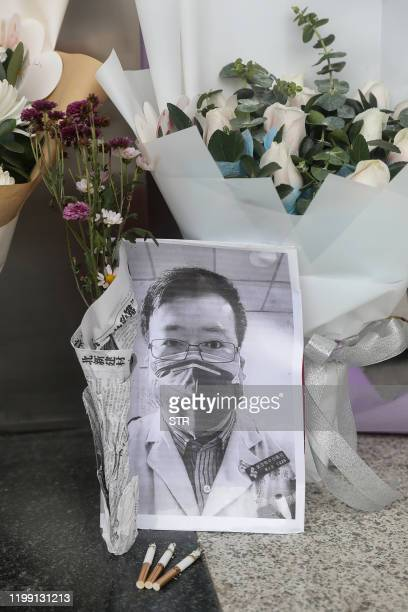 A photo of the late ophthalmologist Li Wenliang is seen with flower bouquets at the Houhu Branch of Wuhan Central Hospital in Wuhan in China's...