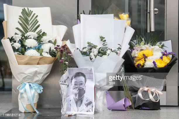 TOPSHOT A photo of the late ophthalmologist Li Wenliang is seen with flower bouquets at the Houhu Branch of Wuhan Central Hospital in Wuhan in...