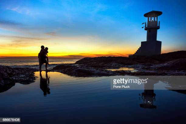 Photo of the night silhouette of the lighthouse and fire plyaer in a bright orange sunset sky, Nang Thong Beach, Khao Lak, Thailand
