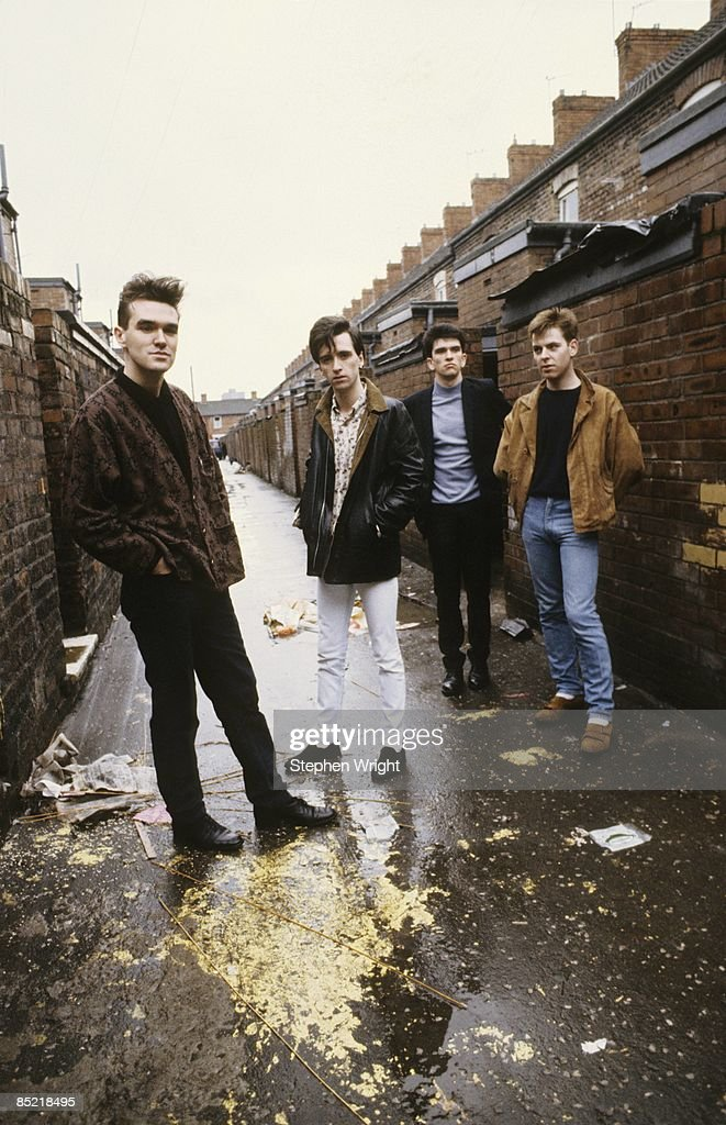 Photo of The Smiths and Andy ROURKE and Mike JOYCE and MORRISSEY and Johnny MARR; L-R: Morrissey, Johnny Marr, Mike Joyce, Andy Rourke - posed, group shot in ginnel / alleyway. Sessions for 'The Queen is Dead'
