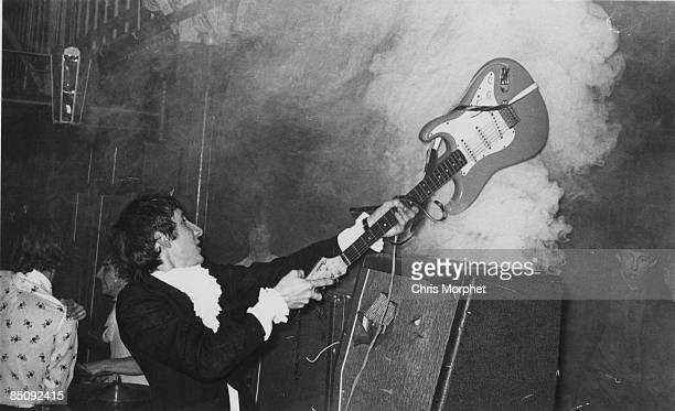 HALLS Photo of The Who and Pete TOWNSHEND Pete Townshend performing on stage smashing guitar against amplifier