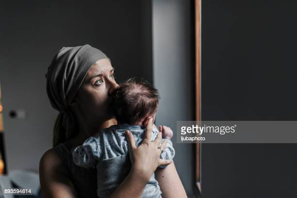 photo of thoughtful woman looking out the window while holding her son - baby depression stock pictures, royalty-free photos & images