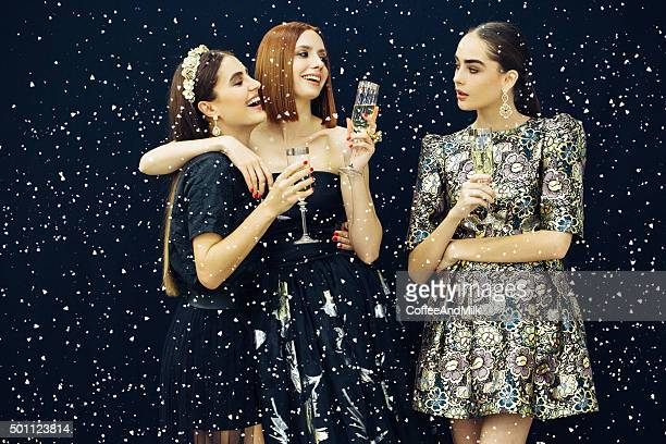 Photo of three laughing girls strewn snow