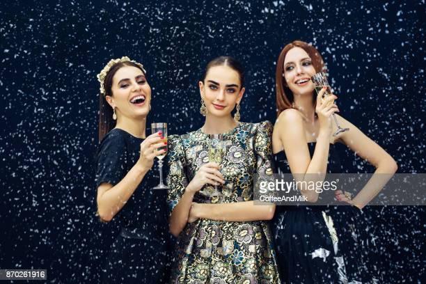 Photo of three laughing girls strewn snow