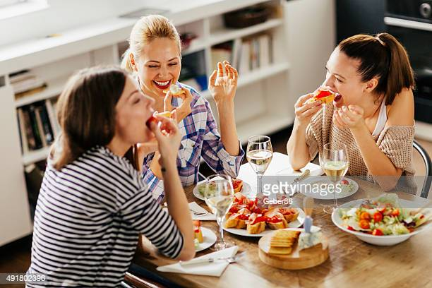 photo of three women enyoing appetizers and wine at home - the brunch stock pictures, royalty-free photos & images