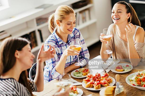 Photo of three women enyoing appetizers and wine at home