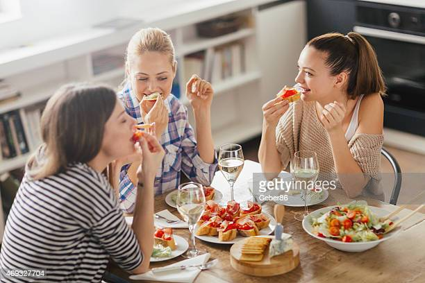 photo of three women enyoing appetizers and wine - the brunch stock pictures, royalty-free photos & images