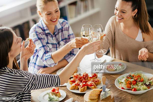 Photo of three young women toasting cheerfully with white wine