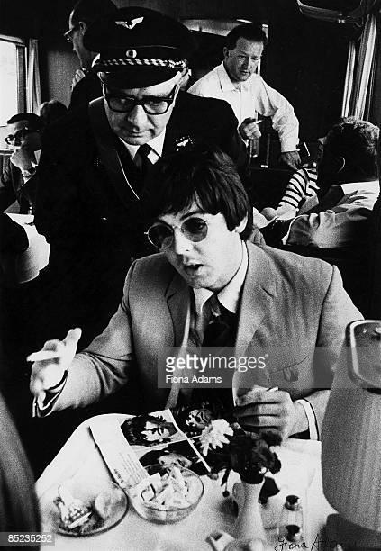 Photo of Tony BARROW and Paul McCARTNEY and BEATLES Paul McCartney on 1966 Germany tour on train between Munich and Hamburg Tony Barrow in background