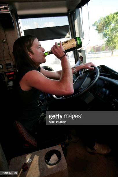 Photo of TOUR BUS and Caleb FOLLOWILL and KINGS OF LEON Caleb Followill at the wheel of the tour bus drink whisky bottle