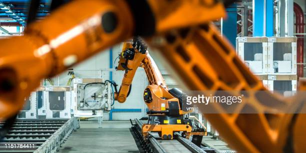 photo of two robotic arms doing work in a factory assembly line - robot arm stock pictures, royalty-free photos & images
