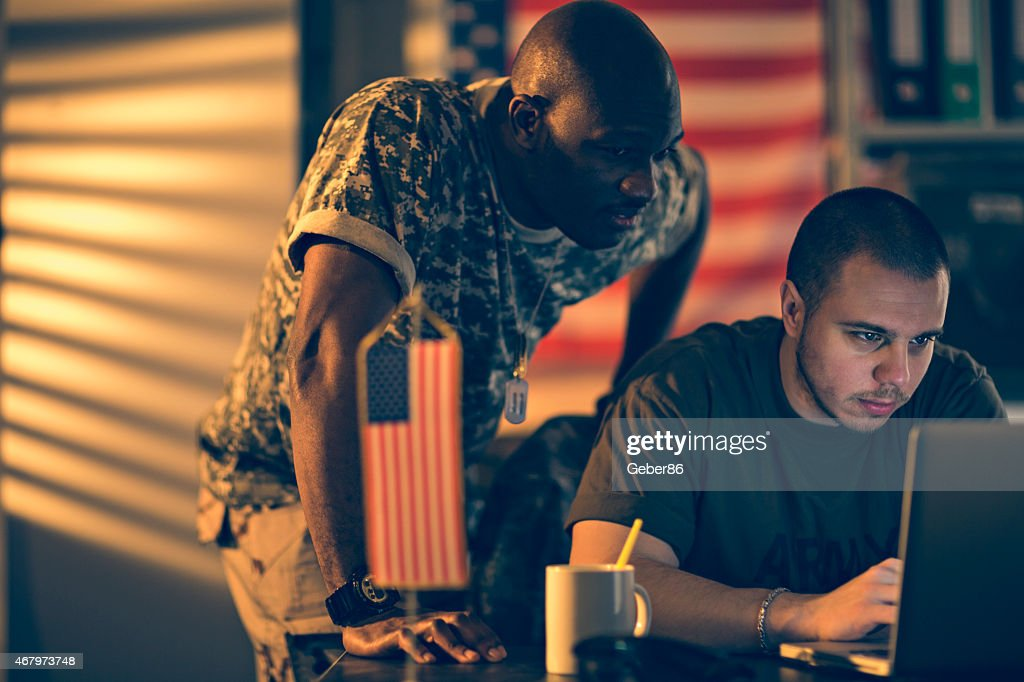 Photo of two young american soldiers looking at laptop : Stock Photo